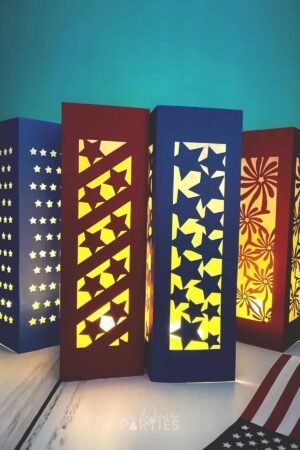 Four patriotic paper lanterns - three with stars designs, and one with fireworks - all glowing in a dark room