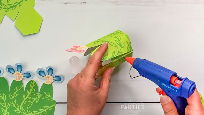 close the flower favor box by glueing the tab to the inside of the box