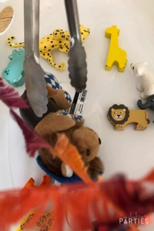 close up of kitchen tongs reaching to grab a stuffed lion