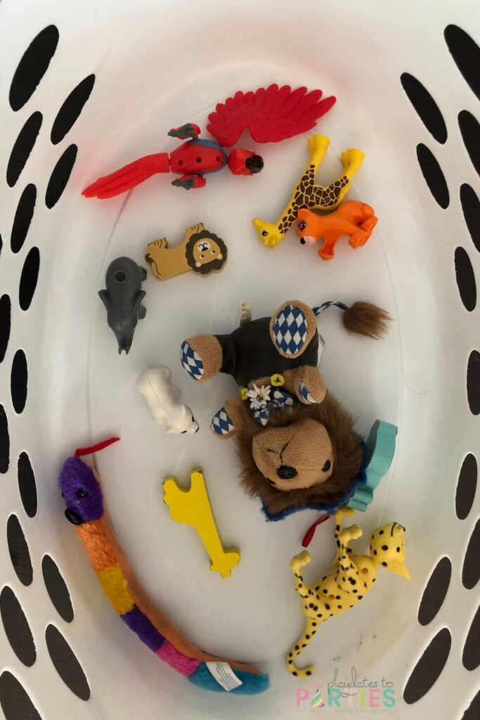 overhead view of laundry basket with toy animals on the bottom