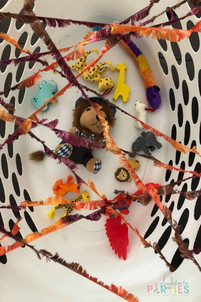 overhead view of laundry basket with toys inside and yarn woven across the top