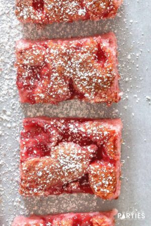 close up overhead view of two pink cherry angel food cake bars sprinkled with powdered sugar on parchment paper