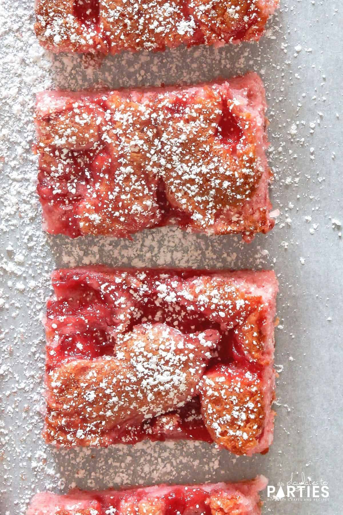 close up overhead view of two pink cherry coconut angel food bars sprinkled with powdered sugar on parchment paper