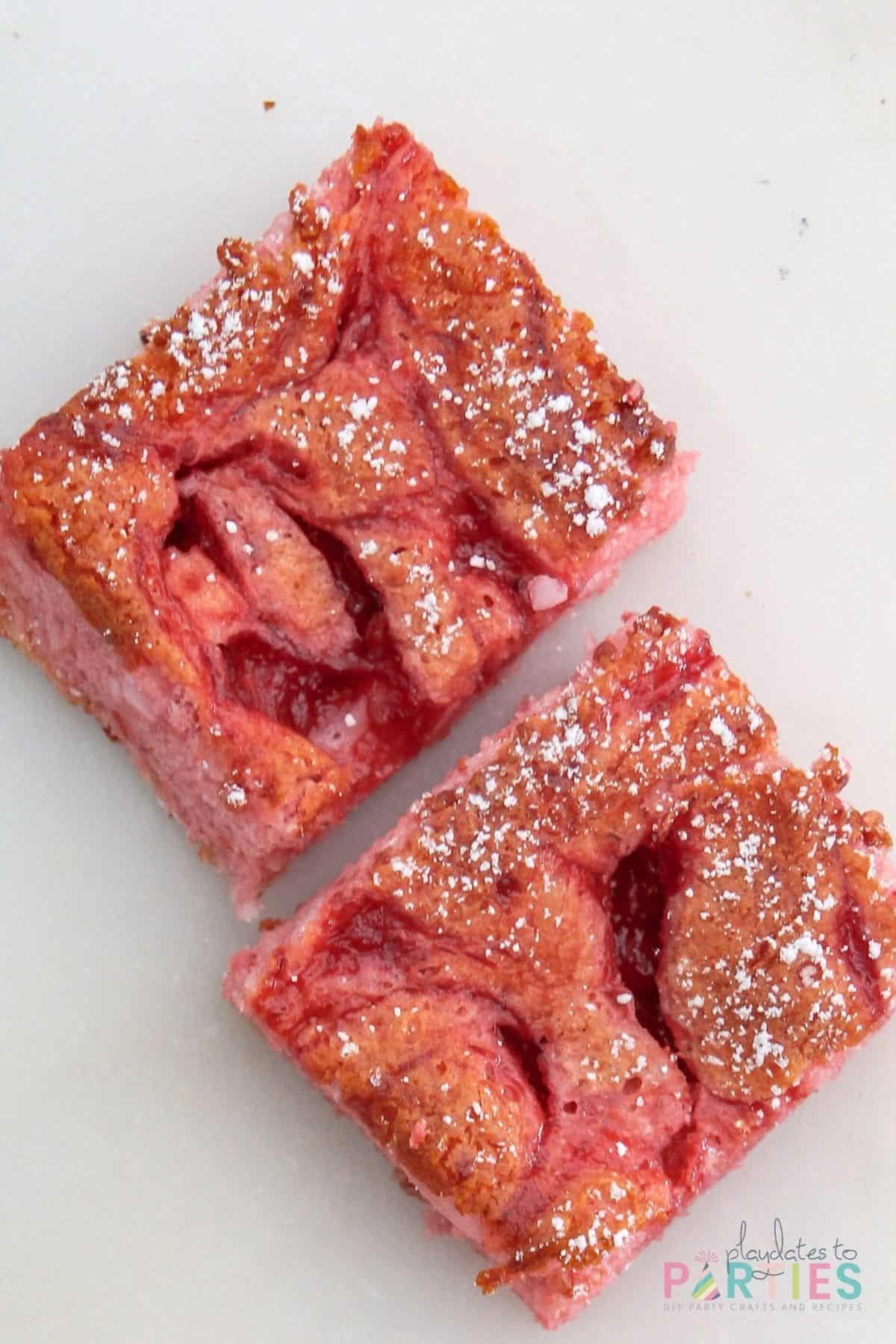 overhead view of two dessert squares on a marble surface with powdered sugar dusted on top.