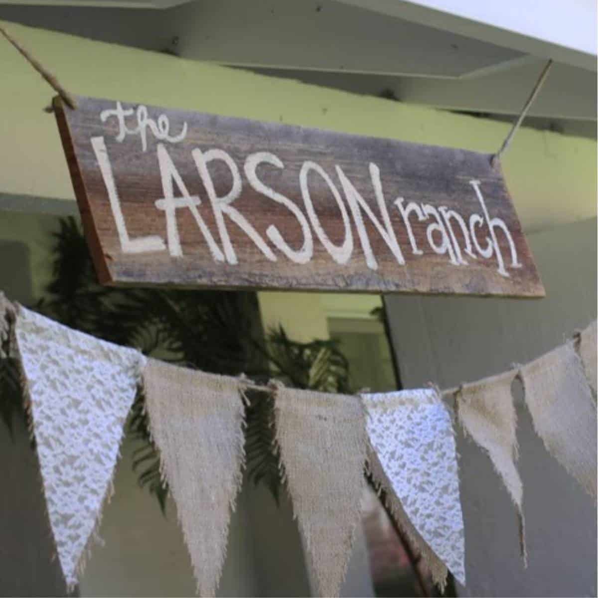 """Handmade wooden sign that says """"The Larson Ranch"""" over bunting made with burlap and lace"""