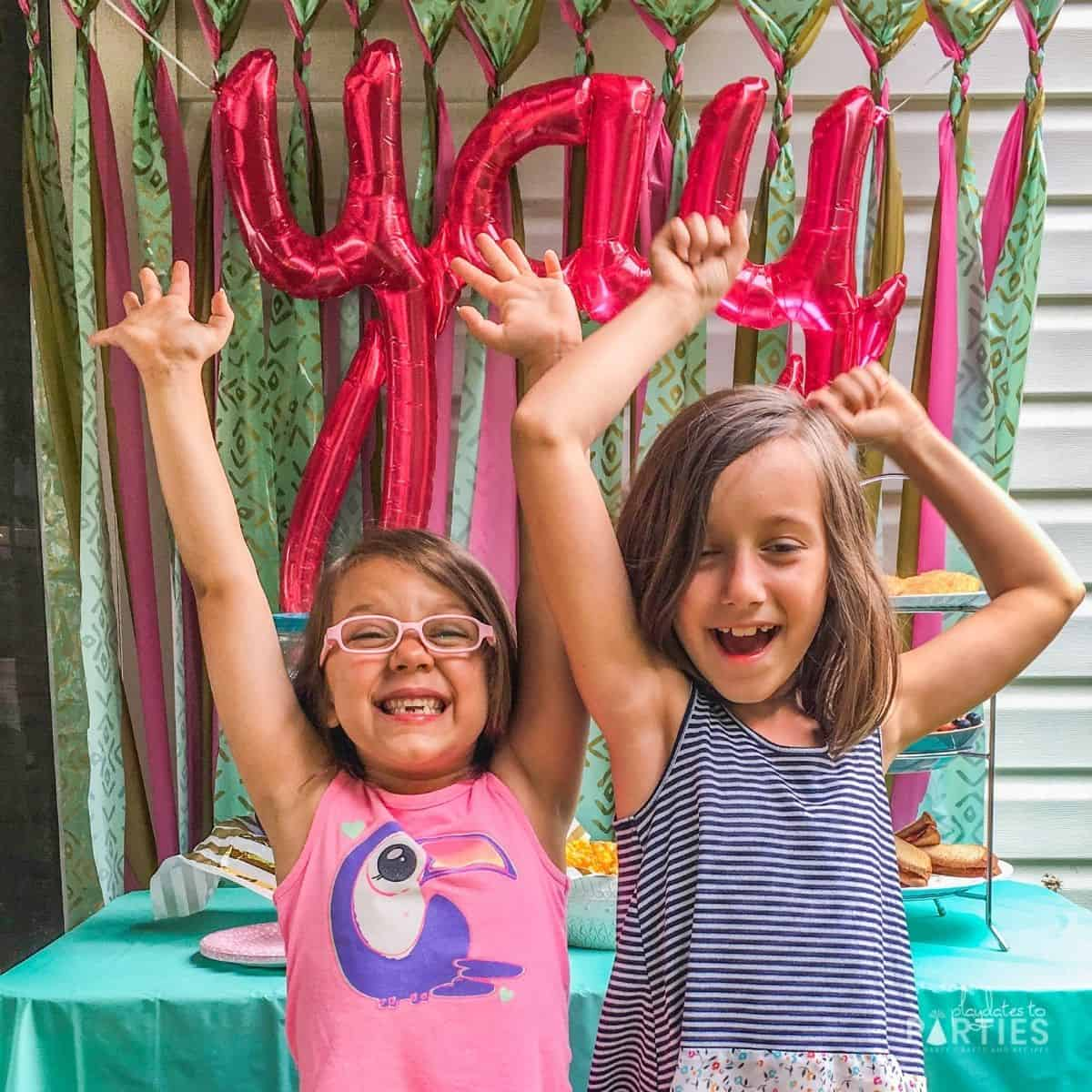 """two girls in front of a party table with a """"yay"""" balloon celebrating the last day of school"""