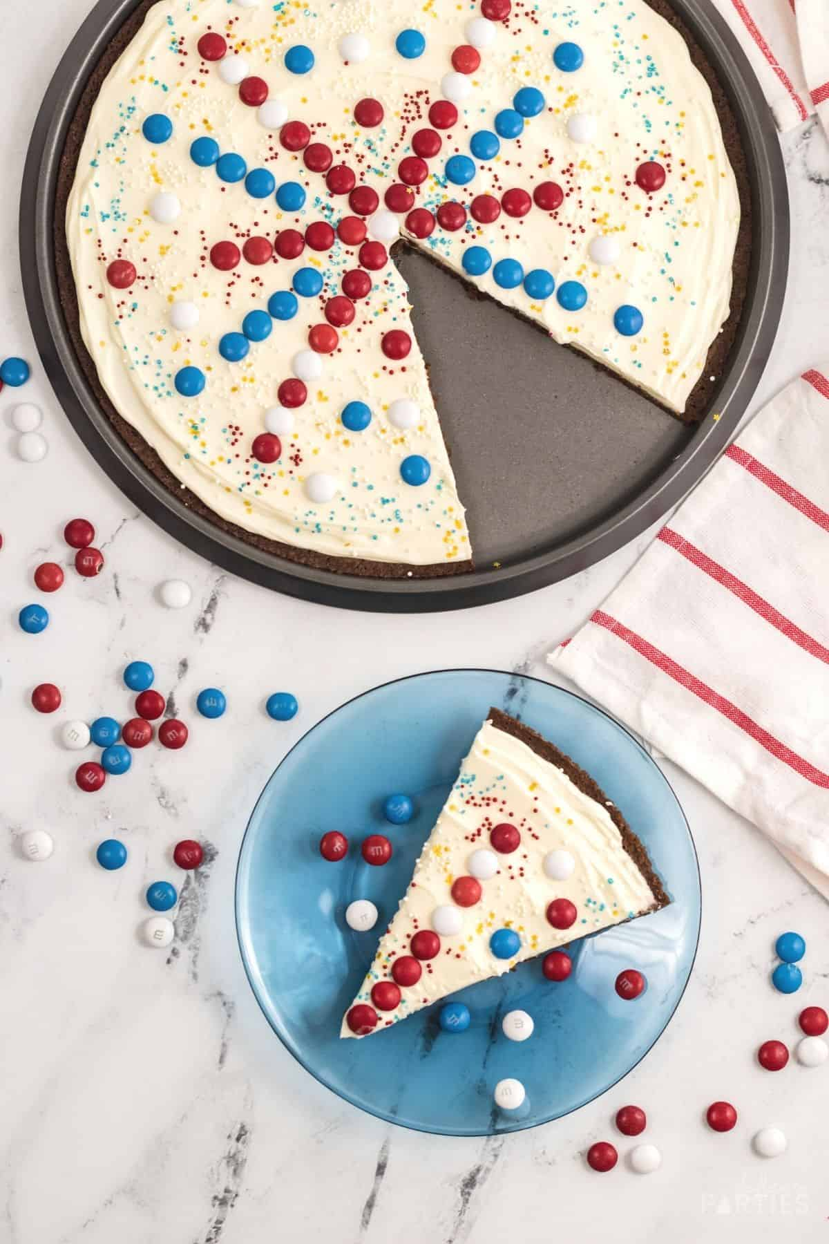 Overhead view of a July 4th dessert pizza with a slice cut out and on a blue plate.