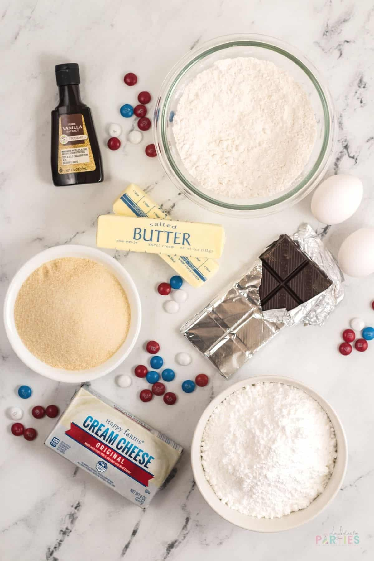 Ingredients for July 4th brownie pizza on a marble surface: vanilla extract, flour, eggs, butter, sugar, baking chocolate, cream cheese, powdered sugar, and candies