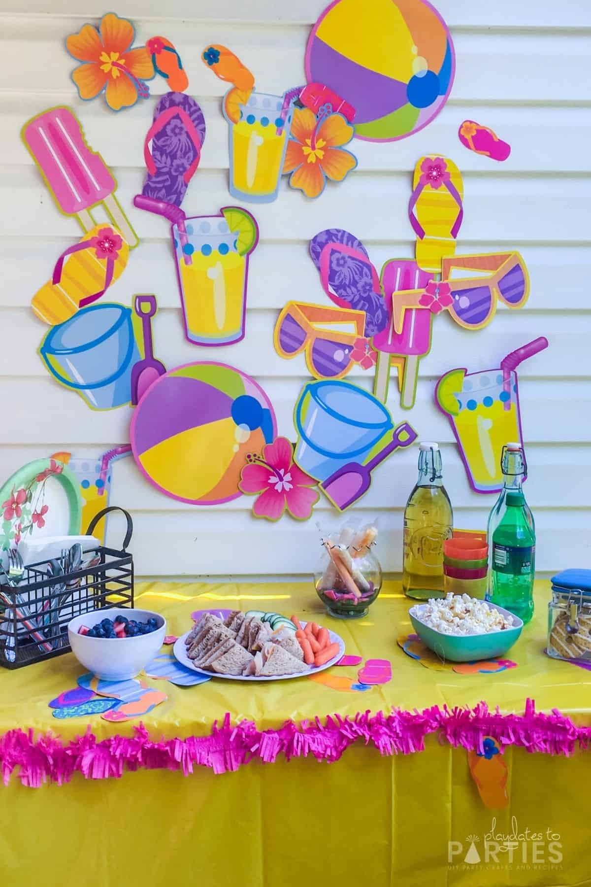 photo of a summer party table with beach themed paper cutouts on the wall, a yellow tablecloth and pink fringe around the edge
