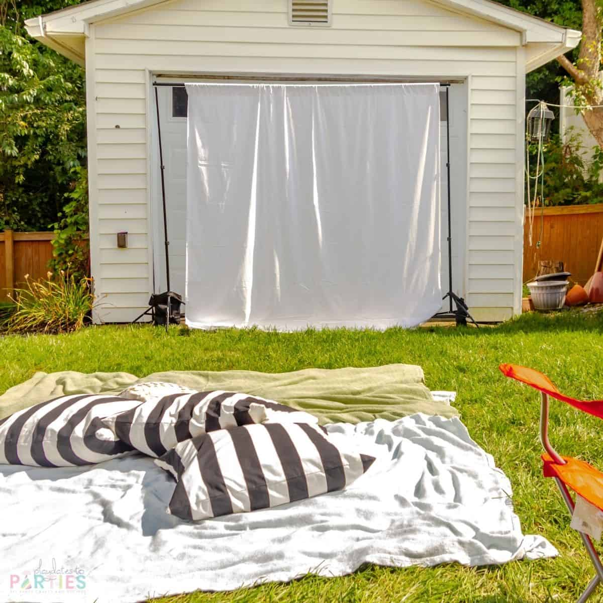 Simple outdoor movie setup with a party backdrop frame, and a white bedsheet. Throw blankets and house pillows provide a place for kids to hang out on the grass.