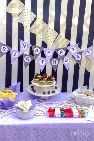 simple dessert table setup with easy store-bought movie snacks for treats on a purple and black themed color scheme, with gold accents