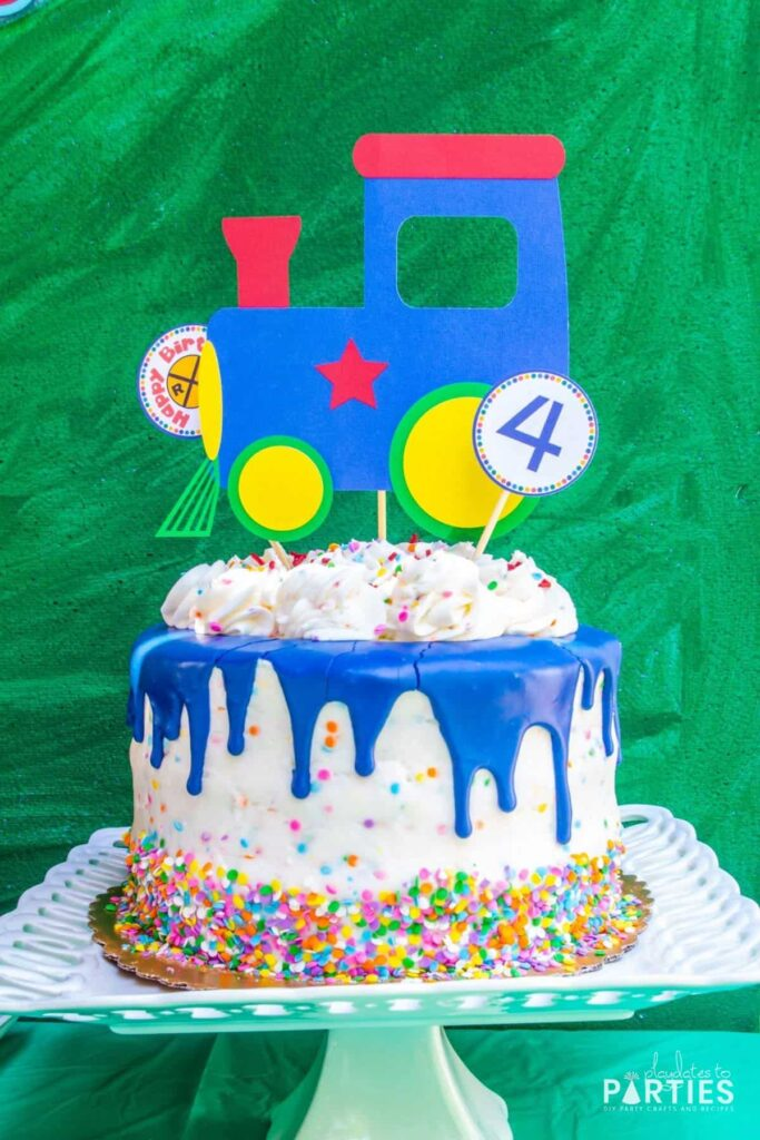 birthday party cake with blue drip icing, multicolored confetti sprinkles, and a paper train engine topper