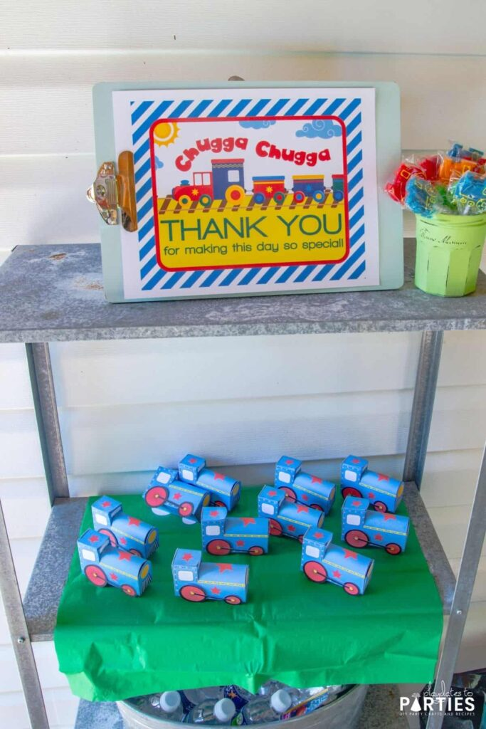 photo of outdoor shelves with mini trains as favor boxes, a jar of train lollipops, and a sign that says Chugga Chugga Thank You