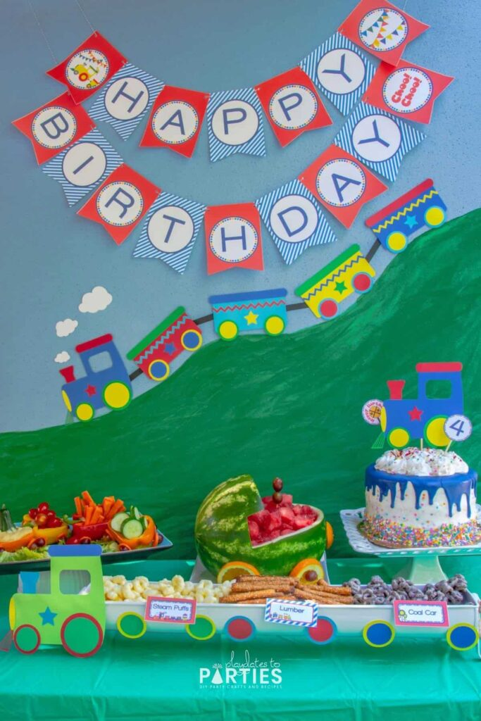 A train birthday party buffet with a variety of themed party food, a happy birthday banner, and other DIY decor
