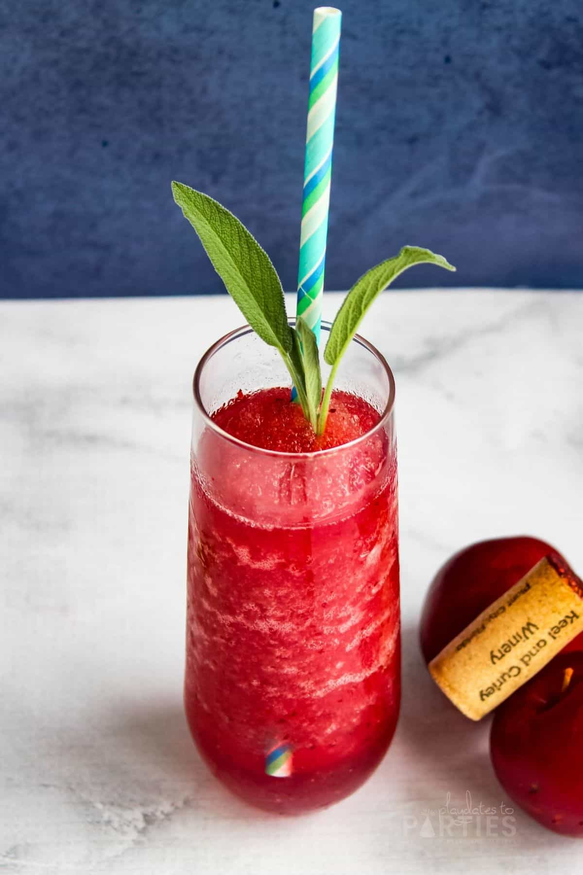 a bright red wine slushie in a stemless champagne flute garnished with basil and a colorful paper straw sitting next to fresh plums