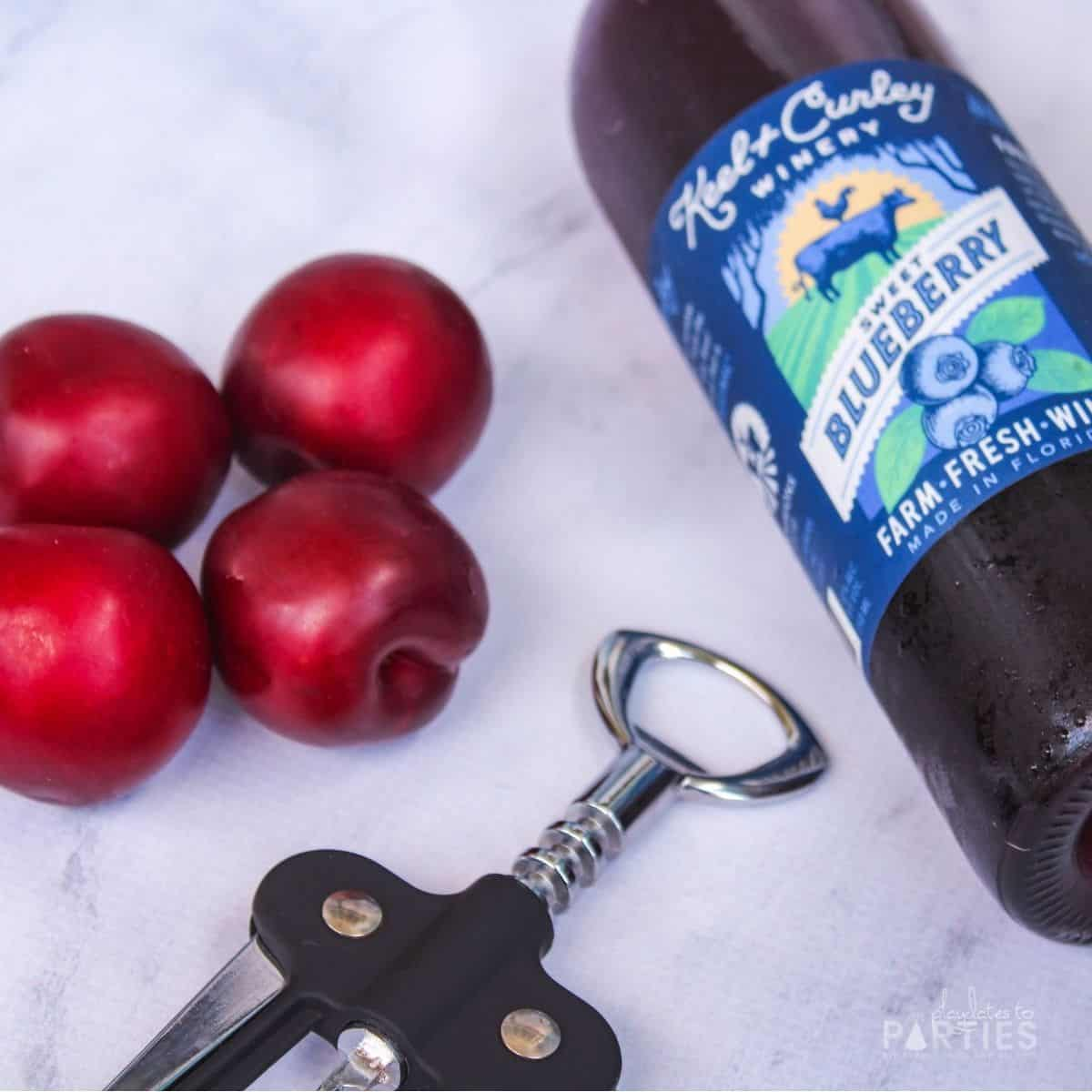 a bottle of wine and four plums on a marble surface next to a wine bottle opener