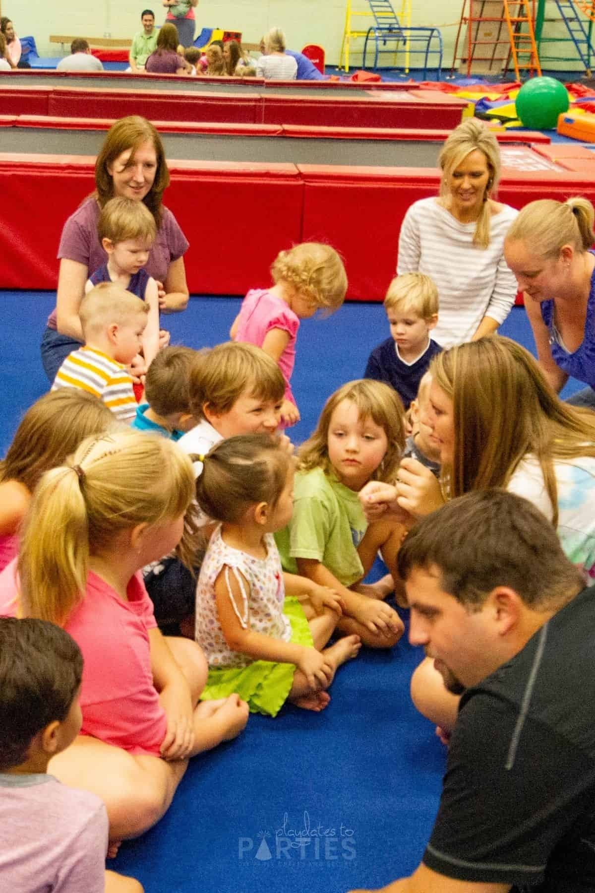 children sitting at a play gym with an instructor leading group play