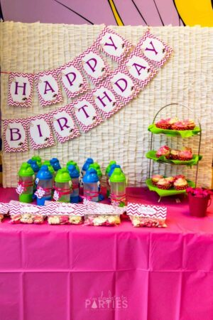 Favor and dessert table with a ruffled backdrop and a gymnastics party banner that says Happy Birthday
