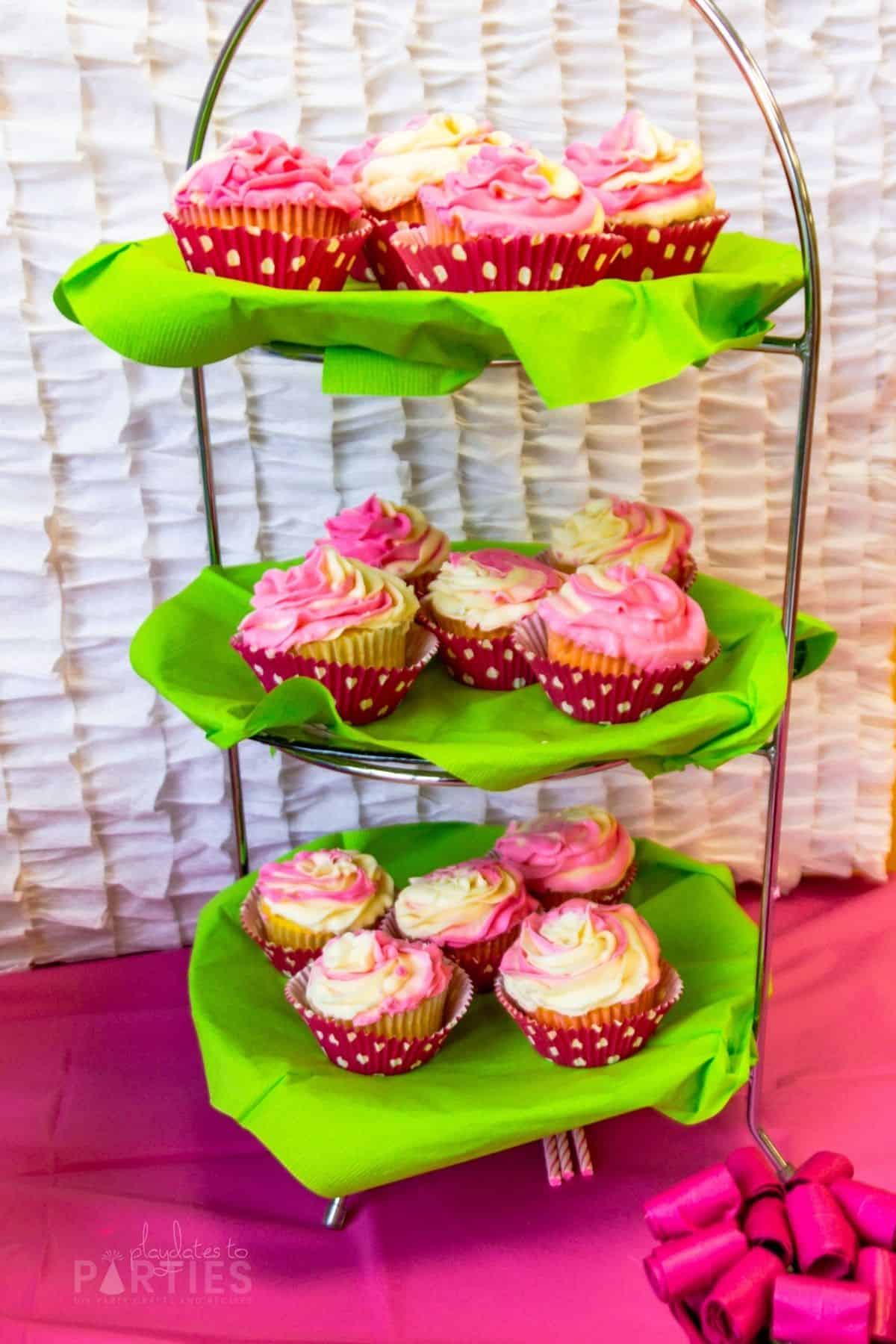 cupcakes on a three tiered tray with white and pink swirl frosting and pink cupcake liners with white polka dots
