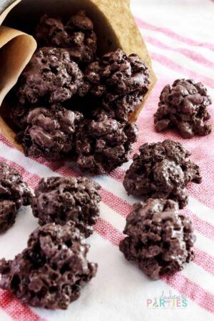 lumps of coal treats spilling out of a jar onto a red and white kitchen towel