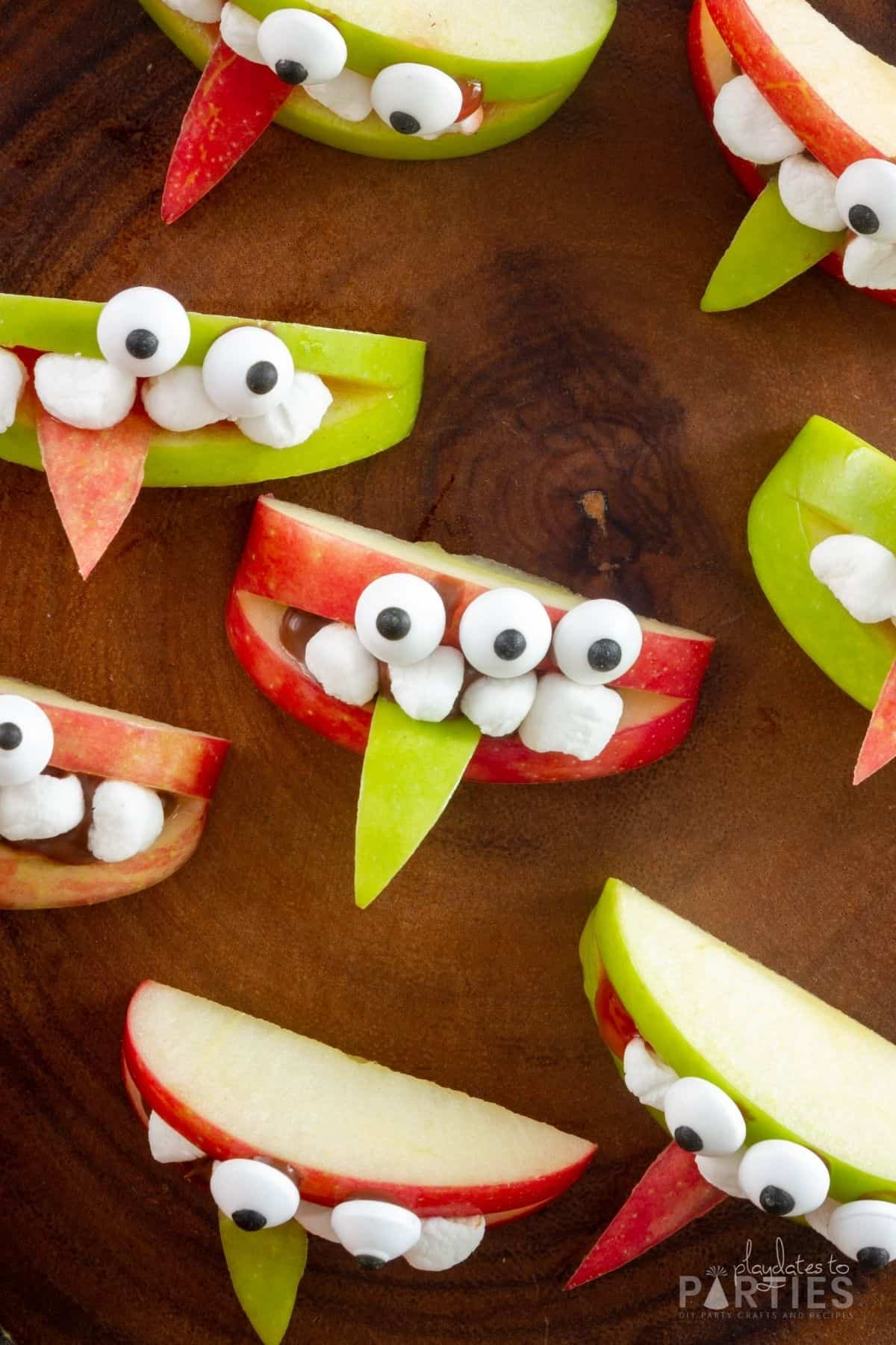 Overhead view of monster apple teeth snacks on a wood serving tray for a Halloween party.