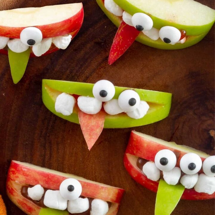 Overhead view of green and red apple wedges decorated with marshmallow teeth and candy eyeballs to look like cute monsters.