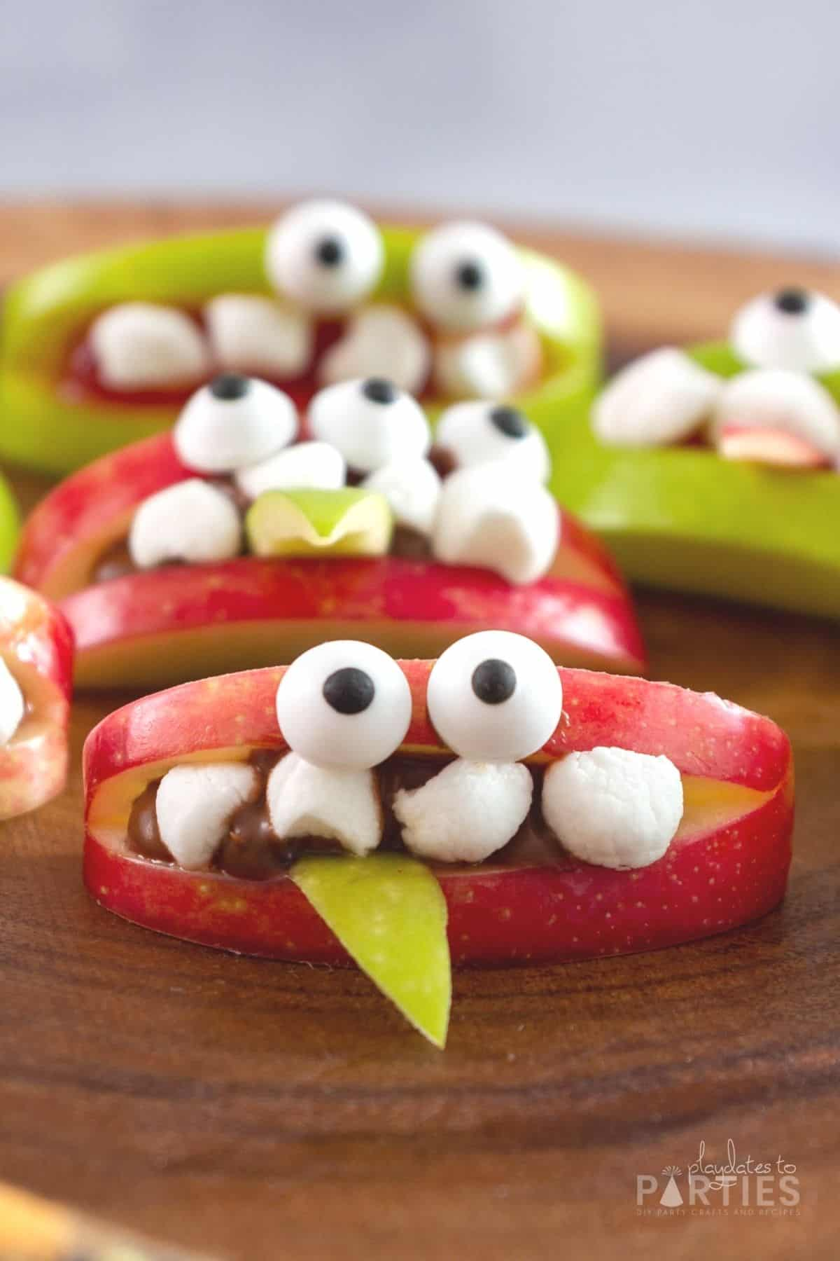 Close up front view of an apple wedge decorated to look like a cute Halloween monster.