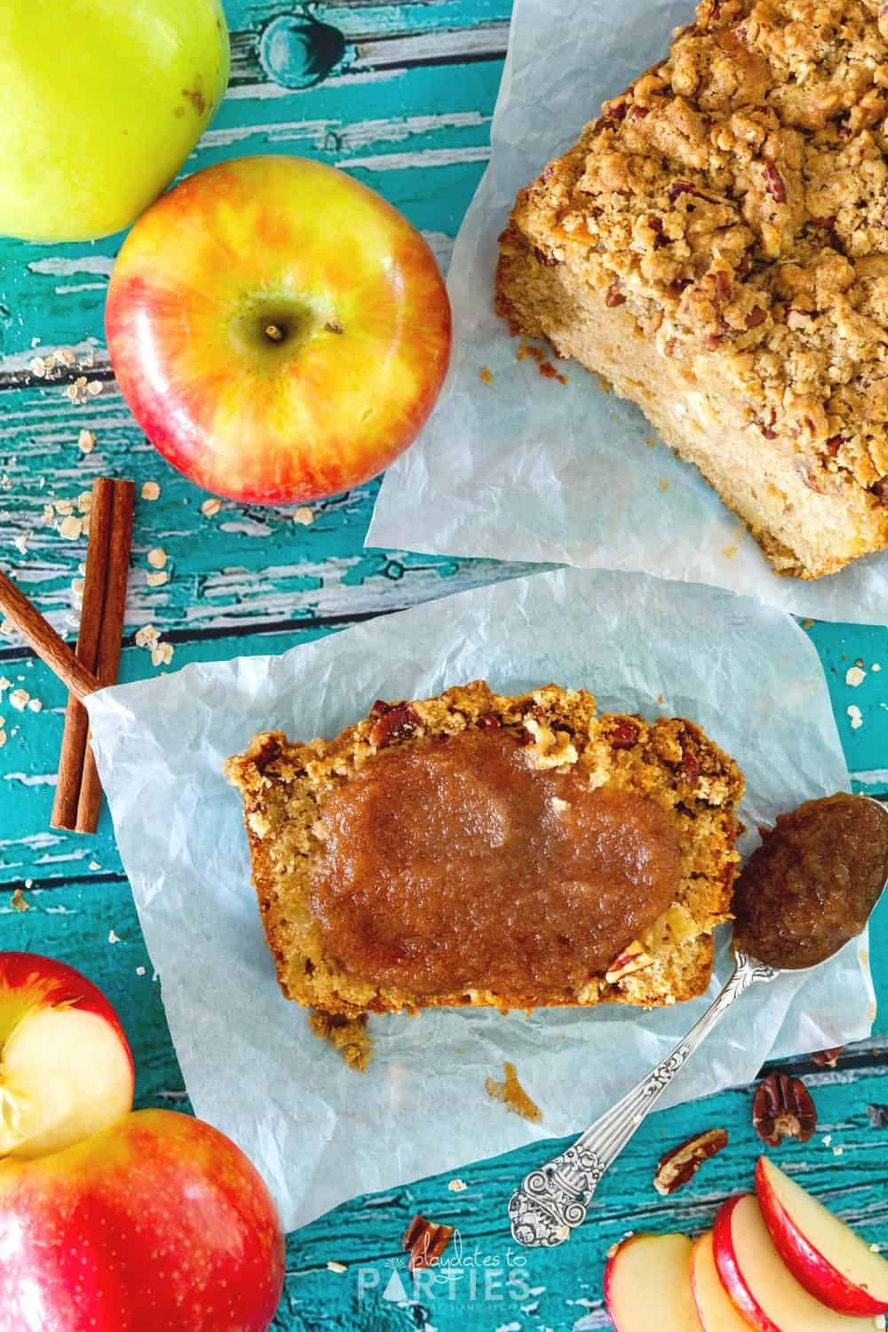 A slice of quick bread with a smear of apple butter on a piece of parchment paper.