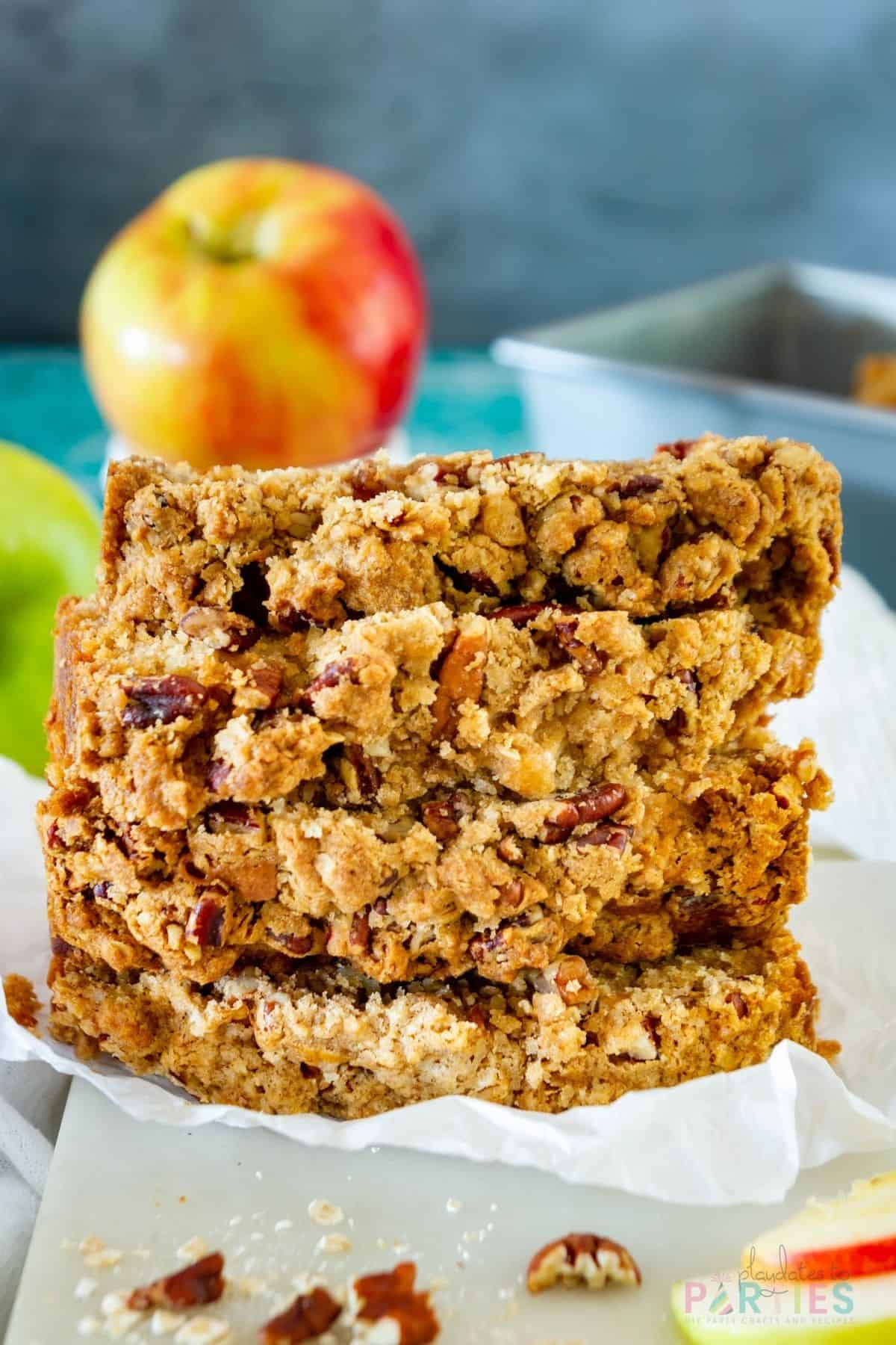 A stack of apple bread slices on a marble board showing the pecan streusel topping.