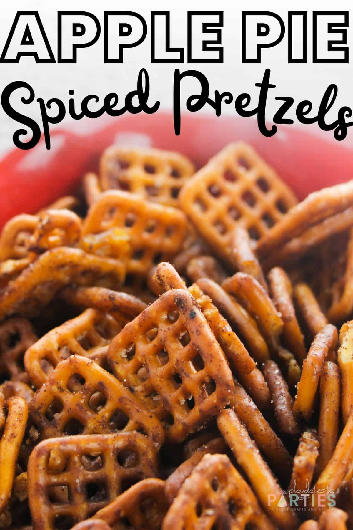 close up image of seasoned pretzels in a red bowl with text overlay apple pie spiced pretzels