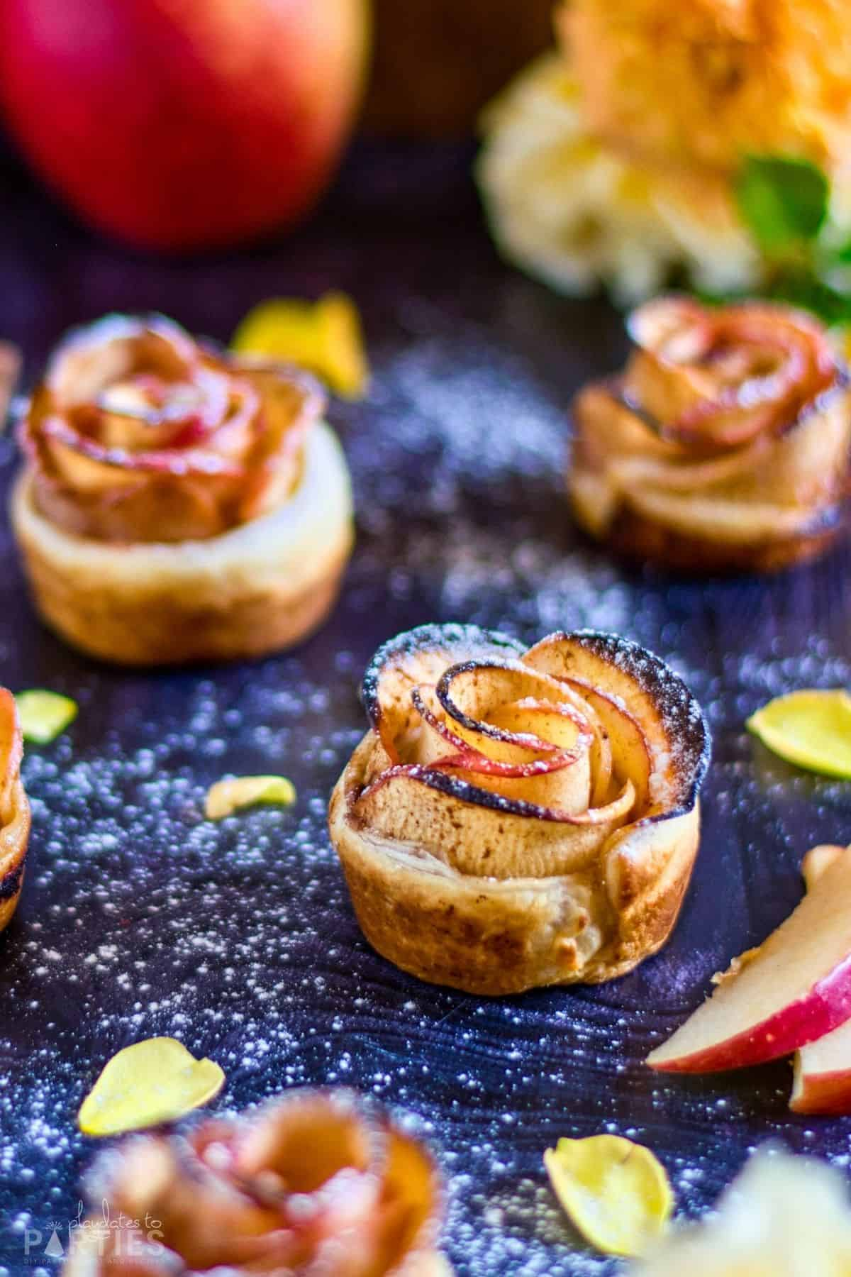 Mini apple tarts on a dark surface surrounded by flower petals