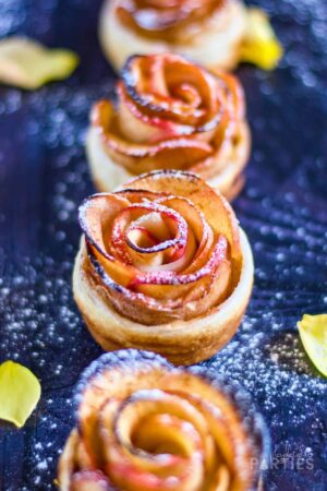 close up of four finished apple roses with puff pastry dusted with powdered sugar