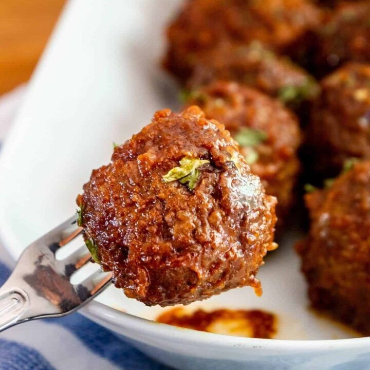 close up of a crock pot apple butter meatball on a cocktail fork with a plate of meatballs in the background