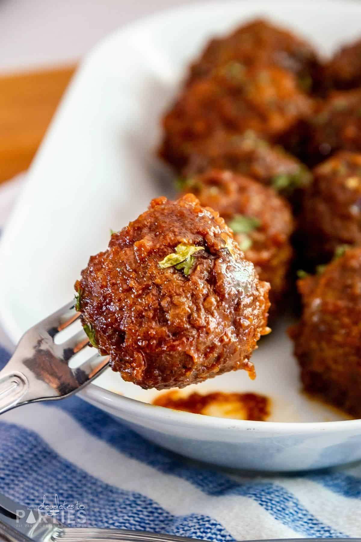 close up of a meatball on a cocktail fork with a plate of meatballs in the background