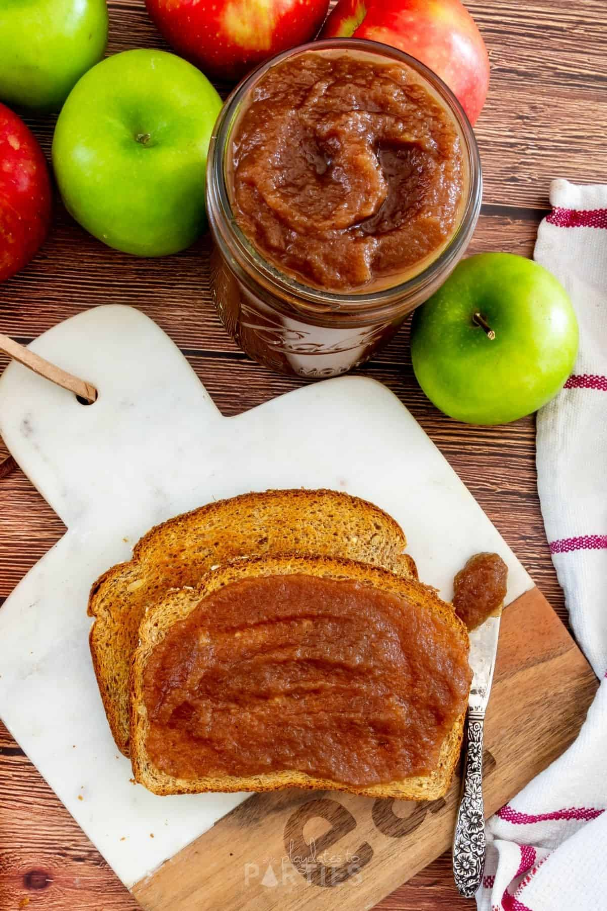 overhead view of toast on a marble cutting board, slathered with apple butter with a tea towel and a jar of apple butter nearby
