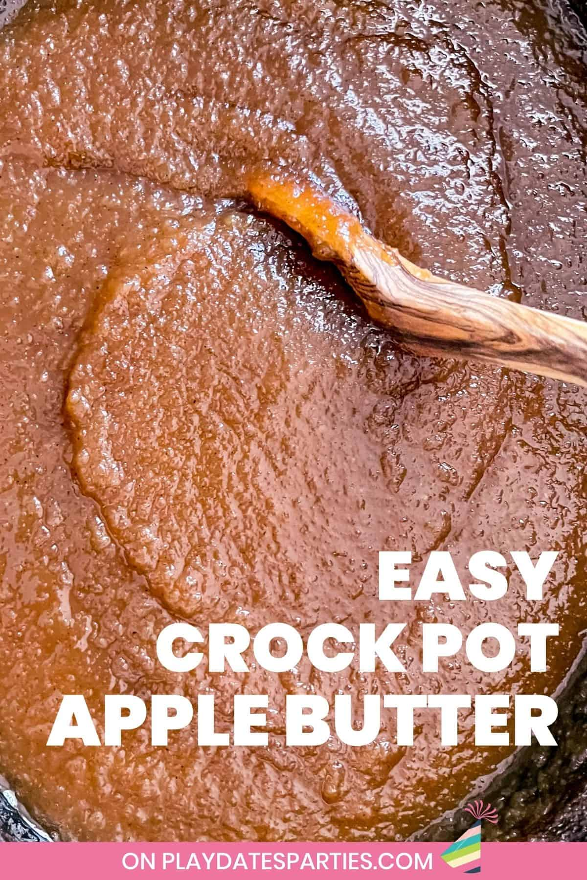 close up of apple butter cooking in a slow cooker and being stirred by a wooden spoon