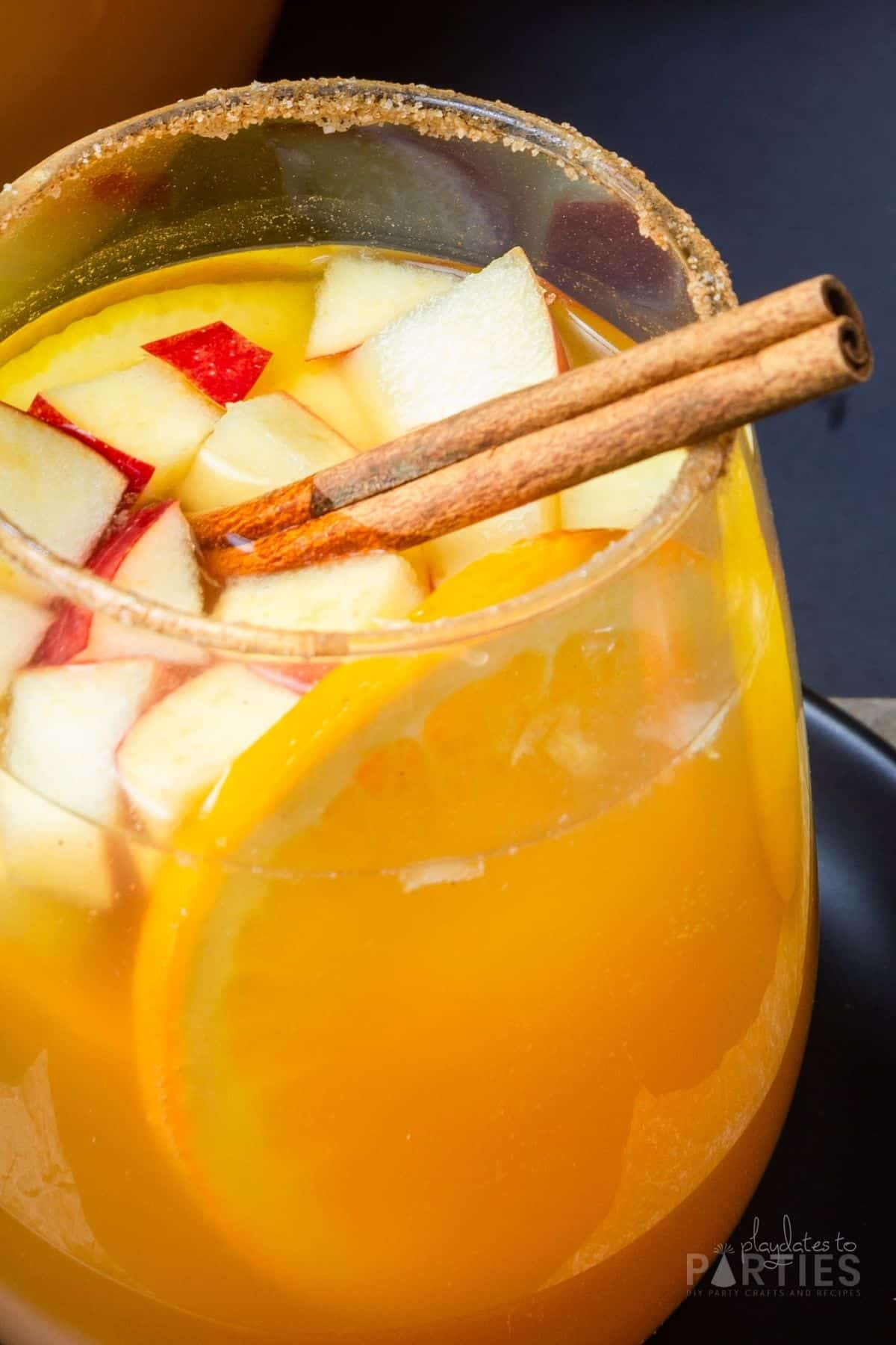 Close up of a glass of sangria with a cinnamon sugar rim and garnished with a stick of cinnamon.