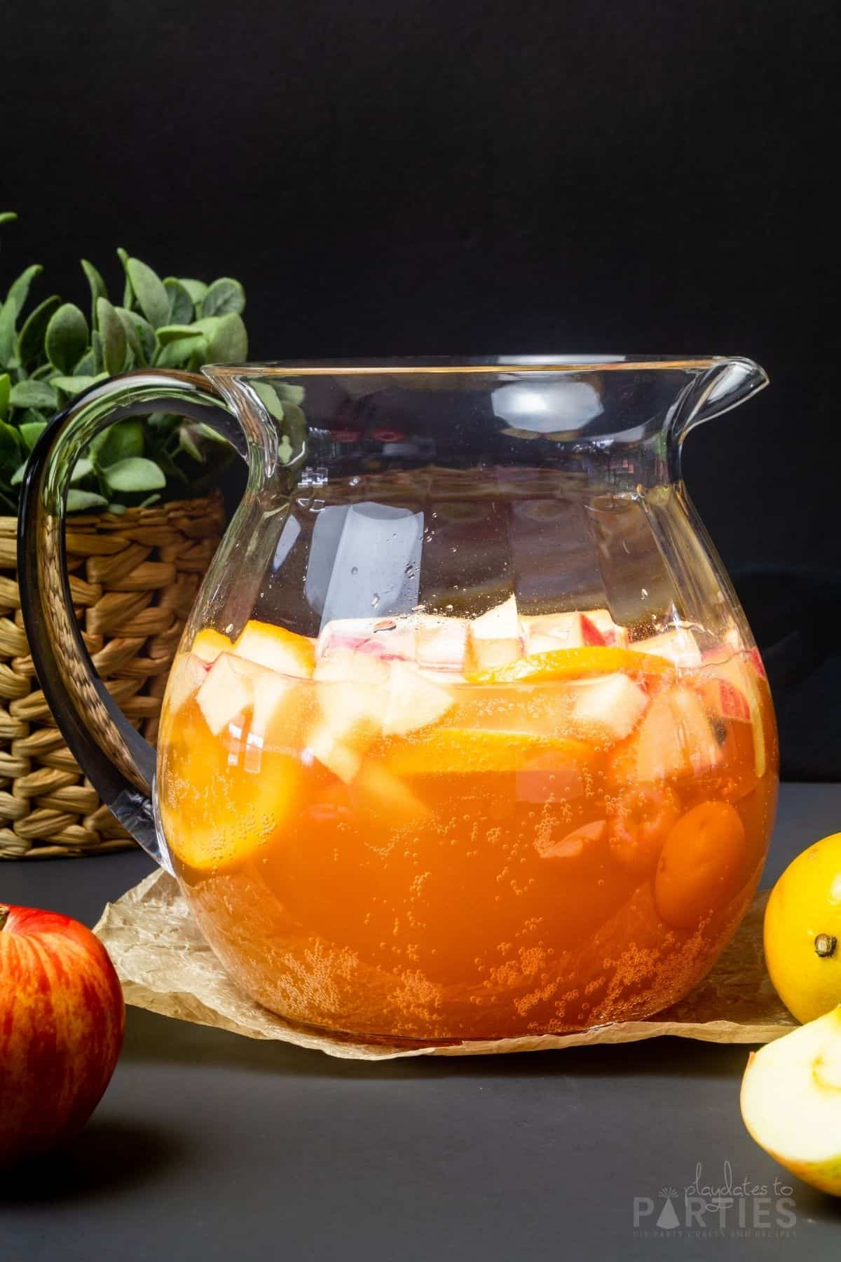 A pitcher filled with apple cider sangria surrounded by apples and lemons.