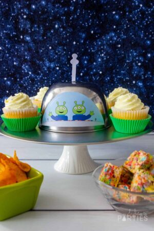 Front view of a UFO party platter with cute aliens waving hello.