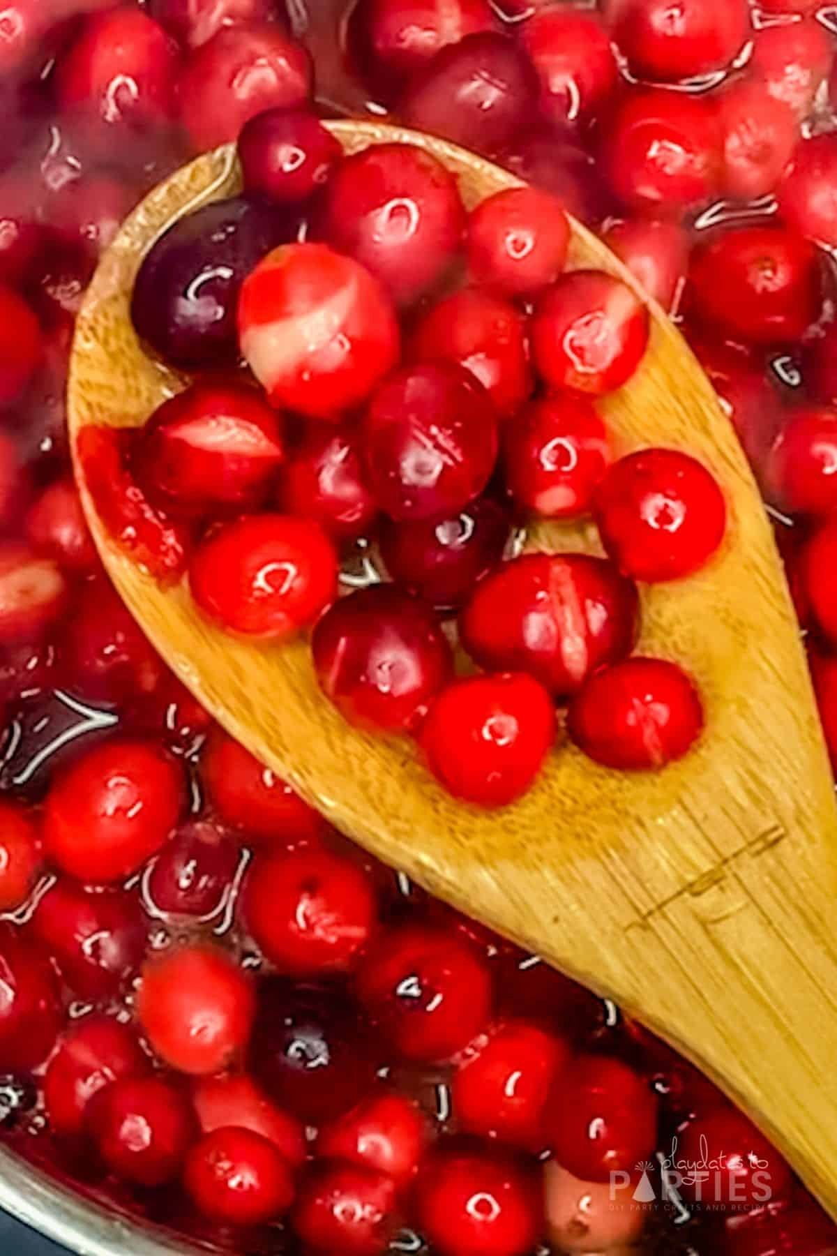 A wooden spoon with cranberries, some of which have popped.
