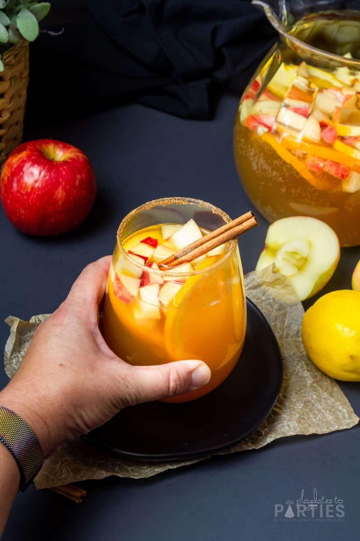 A woman's hand grabbing a glass of spiced apple cider sangria.