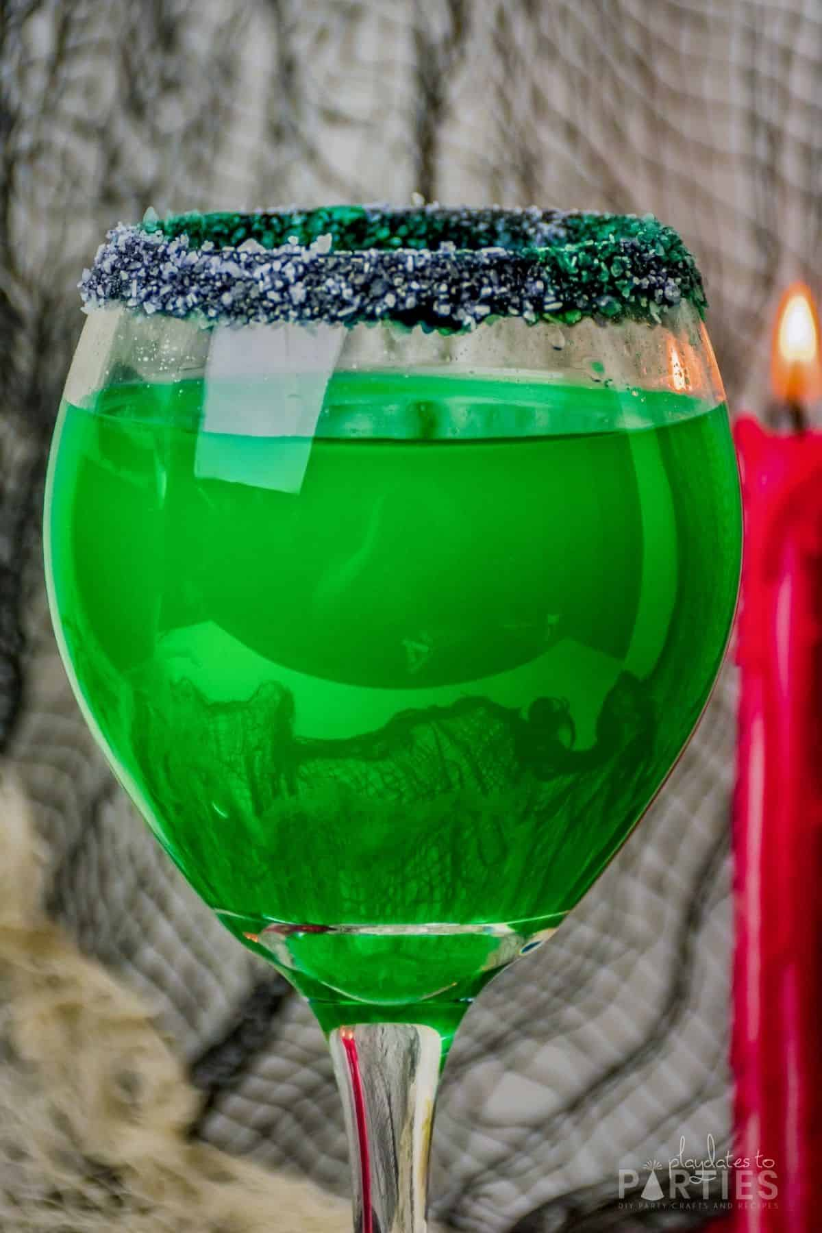 Front view of a large wine glass filled with a green Halloween cocktail.