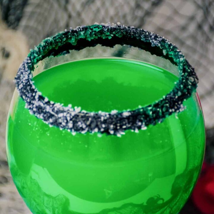 Green Halloween cocktail rimmed with black and white salt.