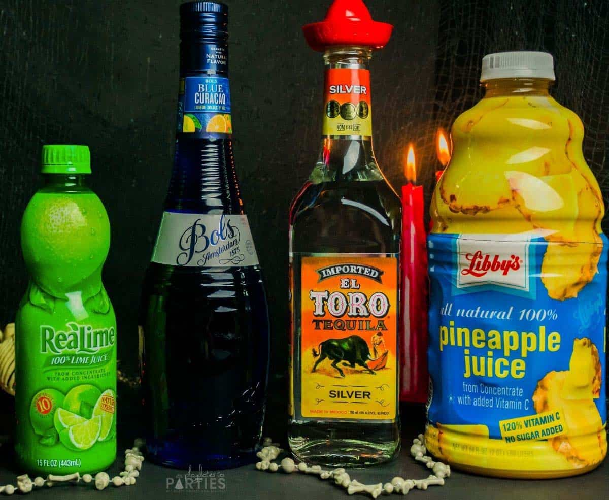 Ingredients for green margaritas: lime juice, blue curacao, tequila, and pineapple juice.