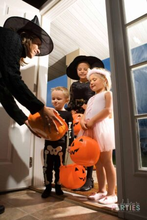 Woman holding out a bucket for trick or treaters.